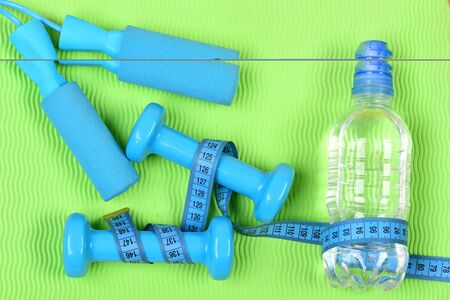 Barbells and skipping rope tied around with measuring tape roll. Dumbbells, cyan jump rope and water bottle on green wavy texture background. Shaping and fitness. Healthy shape and sport concept