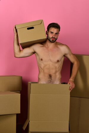Delivery and sexuality concept: naked guy holding carton on shoulder