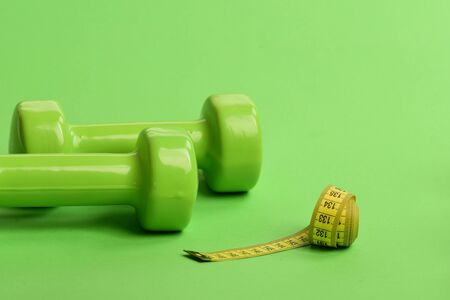 Barbells made of plastic by long soft ruler. Sports equipment and yellow measuring tape in roll. Dumbbells in bright green color isolated on green background, closeup. Shaping and sport regime concept