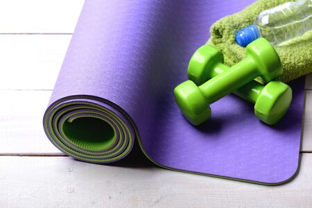 Dumbbells made of green plastic on light wooden background. Sports and healthy lifestyle concept. Shaping and fitness equipment. Barbells near water bottle and soft towel lying on purple yoga mat 免版税图像