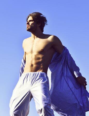 Caucasian macho in blue striped pajamas on blue sunny sky background Banco de Imagens