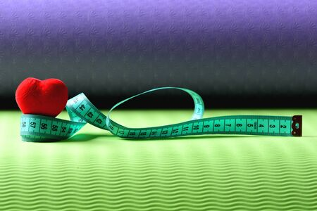Heart decoration and flexible ruler lying on yoga mat