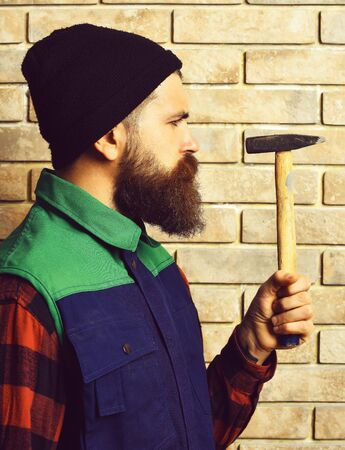 bearded builder man, long beard, brutal caucasian hipster with moustache in black cap holding hammer with serious face on brick wall studio background Banco de Imagens