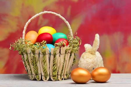 spring easter holiday, colorful eggs, golden egg in basket, rabbit 免版税图像
