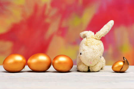 rabbit toy and easter golden eggs on colorful background