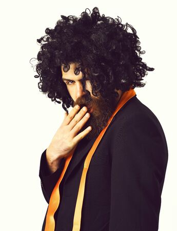 Bearded man, long beard. Brutal caucasian shy hipster with moustache have acid orange tie on suit and black curly afro wig isolated on white studio background