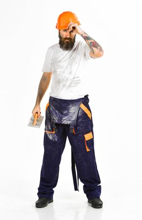 Repairman at work concept. Bearded repairman on serious face and dirty boilersuit, white background. Plasterer, repairman, foreman in helmet, hard hat holds putty knife, plastering tool, ready to work