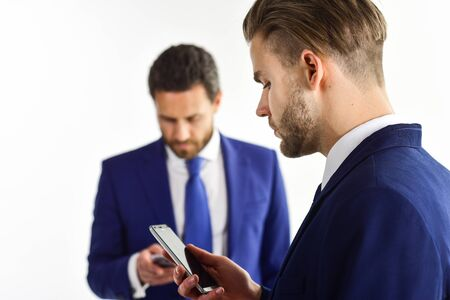 Men in suit or businessmen with busy face hold smartphone