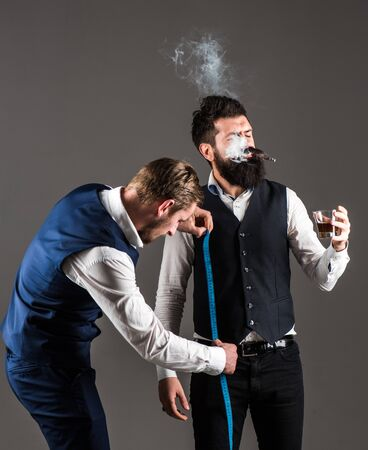 Tailor taking measurements for sewing suit, grey background. Man with measuring tape busy. Client with beard and strict face smoke cigar and drink whiskey while tailor working. Exclusive wear concept.