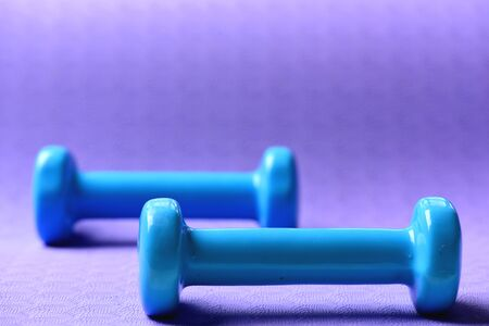 Healthy shape and sport concept. Shaping and fitness equipment. Barbells made of plastic, close up. Dumbbells in cyan blue color on purple background, selective focus 免版税图像