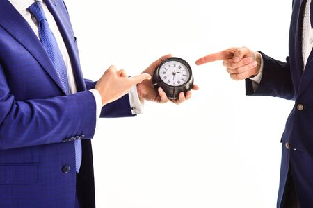 Business and discipline concept. Hands of two caucasian men with index fingers pointing at clock on white background. Male hand in suit holds clock, copy space. Partners came at meeting just in time. Archivio Fotografico
