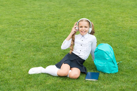 small girl hold book. literature for kids. childhood developing. work with notebook. back to school. kid study in park. relax on green grass with book. listening music online. copy space