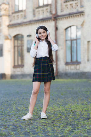 Sound learning. Happy child listen to sound file in headphones. Small girl enjoy music outdoors. Music school. Hi-Fi stereo sound. Sound technology. Listening comprehension. Modern life