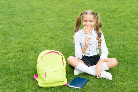 knowledge day. modern school education. happy childhood. teen girl with book. pretty child little girl eat sweet lollipop. study literature for children. learn with document folder