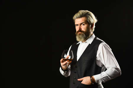 Matured in sherry casks. Whisky tasting. Good indication of condition of whisky. Bearded businessman in elegant suit with glass of whisky. Sommelier tastes expensive drink. Elegant macho drink cognac 写真素材