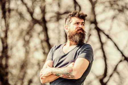 Man attractive bearded hipster posing outdoors. Confident posture of handsome man. Guy masculine appearance with long beard. Barber concept. Beard grooming. Beard care. Masculinity and manliness