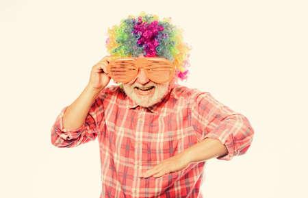 Having fun. Funny lifestyle. Fun and entertainment. Comic grandfather concept. Nice joke. Grandpa always fun. Elderly clown. Man senior bearded cheerful person wear colorful wig and sunglasses.