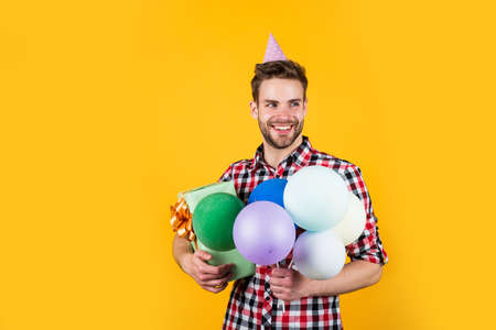 Leisure time. happy holiday celebration. time for fun and presents. happy birthday or anniversary. feel cheer and joy. pure party goer. funny man in birthday cap. guy hold festive balloons