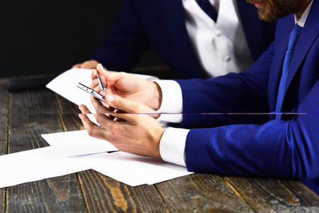 Hands with smartphone on desk. Formal suit, smartphone, documents on black background. Business people and new technolohies. IT, paper work, office employees. Business, innovation, profession concept.