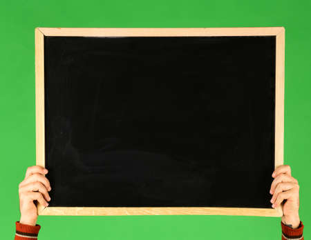 Male hands hold blackboard on green background. Chalkboard with empty space in guys hands, copy space. Advertisement and presentation concept