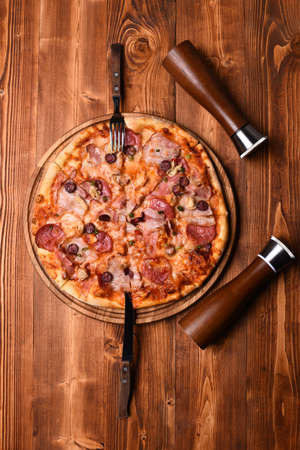 Pizza with bacon and cheese on wooden background, top view. Served table in Italian restaurant, cafe or pizzeria. Fast food concept. Italian dish with fork and knife, salt and pepper containers. Reklamní fotografie