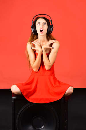 Girl with loose hair wears headphones and red dress.