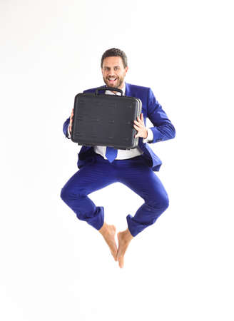 Excited business man with briefcase jumping in mid-air