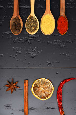 Wooden spoons with paprika, turmeric, herbs and pepper by cinnamon, anise, dry orange slice and chili. Set of spices on dark grey wood background. Food art concept. Composition of condiment, top view 版權商用圖片