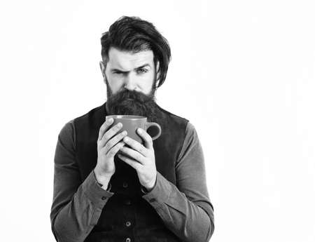bearded man holding cup with coffee, tea with serious face