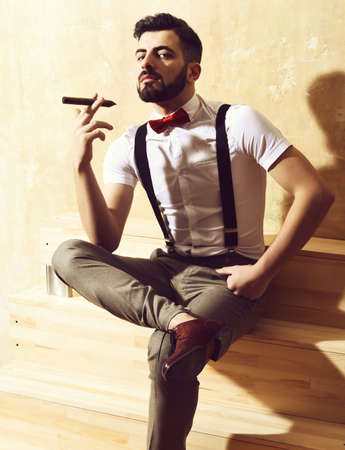 bearded man sitting on wooden stairs with serious face