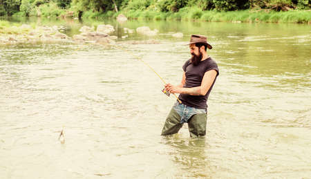 Fisher with fishing equipment. Fisher weekend activity. Fish on hook. Leisure in wild nature. Fishing masculine hobby. Brutal man wear rubber boots stand in river water. Fun of fishing is catching.