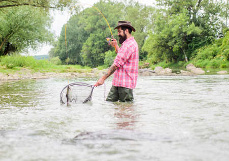 Fishing hobby. If fish regularly you know how rewarding and soothing fishing is. Fishing is an astonishing accessible recreational outdoor sport. Bearded brutal fisher catching trout fish with net Stock Photo