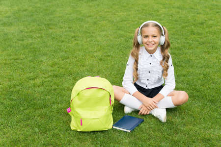 small girl hold book. literature for kids. childhood developing. work with notebook. back to school. kid study in park. relax on green grass with book. listening music online Reklamní fotografie