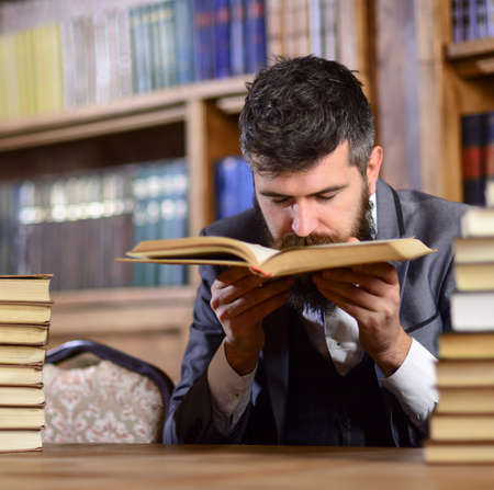 Man with beard in classic suit, scientist or professor sniffs Фото со стока