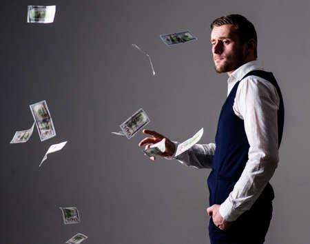 Man in formal wear, businessman throwing money on grey background.