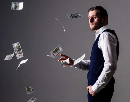 Man in formal wear, businessman throwing money on grey background. Stock Photo