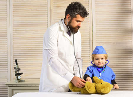 Vet and little assistant examine teddy bear. Man and boy
