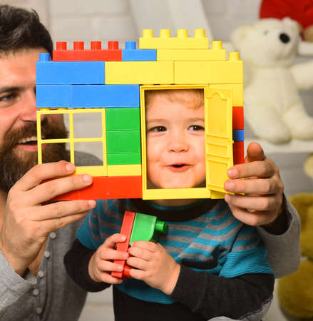 Father and son with surprised faces hold colorful blocks house