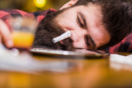 Man with sleeping face alone at bar counter, put head on table. Hipster fall asleep after sniffed cocaine, drug. Guy sleep with rolled banknote in nostril, defocused background. Overdose concept.