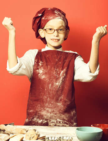 stained cute cook chef boy on red studio background
