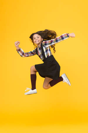 Feel inner energy. Girl with long hair jumping on yellow background. Carefree kid summer holiday. Time for fun. Active girl feel freedom. Fun and jump. Happy childrens day. Jump concept. Break into