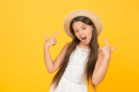 Enjoying warm day. happy childhood. cool little girl wear straw hat. beach fashion for kids. small child on yellow background. holiday joy and activity. beauty. long-awaited summer vacation Standard-Bild