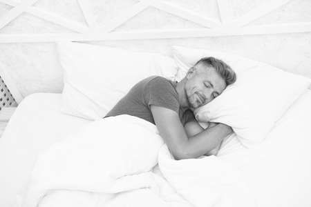 Peaceful mature man relaxing. Good Sleep is Reachable Dream. World Sleep Day. Benefits of good and healthy sleep. Breathe Easily, Sleep Well. Handsome man in bed. Sleeping guy at home. Need more rest Reklamní fotografie