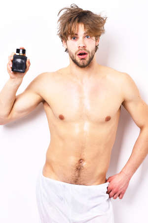 Macho with beard and sexy body holds perfume bottle.