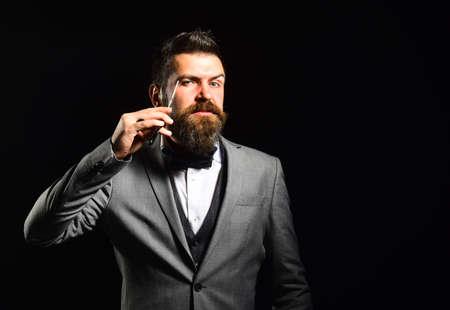Macho in formal suit shaves beard. Man with long beard 免版税图像