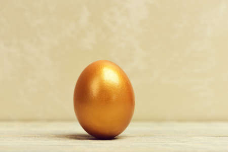 traditional egg painted in golden metallic color on grey background, happy easter concept, luxury and success, birth and future life, business and finance, antique art and retirement Stock Photo
