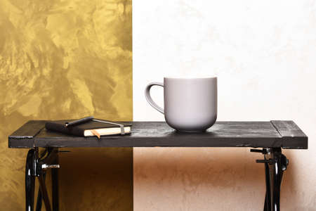 Work and education concept. Cup of tea or coffee and diary on stylish background. Hot drink and notebook with bookmark on low table near wall. Gray cup and notebook with pen on small black table. Фото со стока