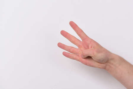 Count down and numbers concept. Male hand shows four fingers. Hand gesture expresses numbers. Hand isolated on light grey background, copy space.
