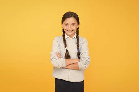 Congratulations. smart little girl on yellow background. knowledge day. childhood happiness. education concept. back to school. happy girl in school uniform. kid fashion. school market