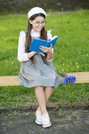 Practice makes perfect. Little girl read book on park bench. Reading homework. Homework assignment. School and education. School homework routine. Homework develops study habits. Learning environment